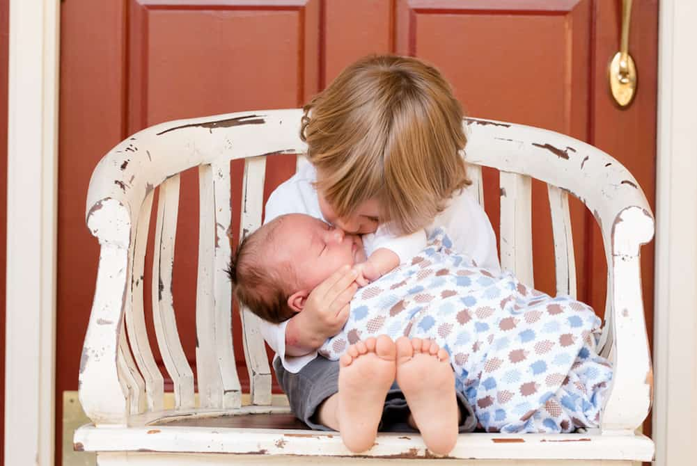 brother kissing baby prepare toddler