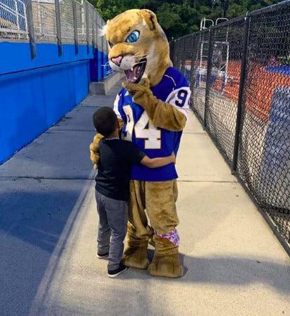 kid hugging mascot