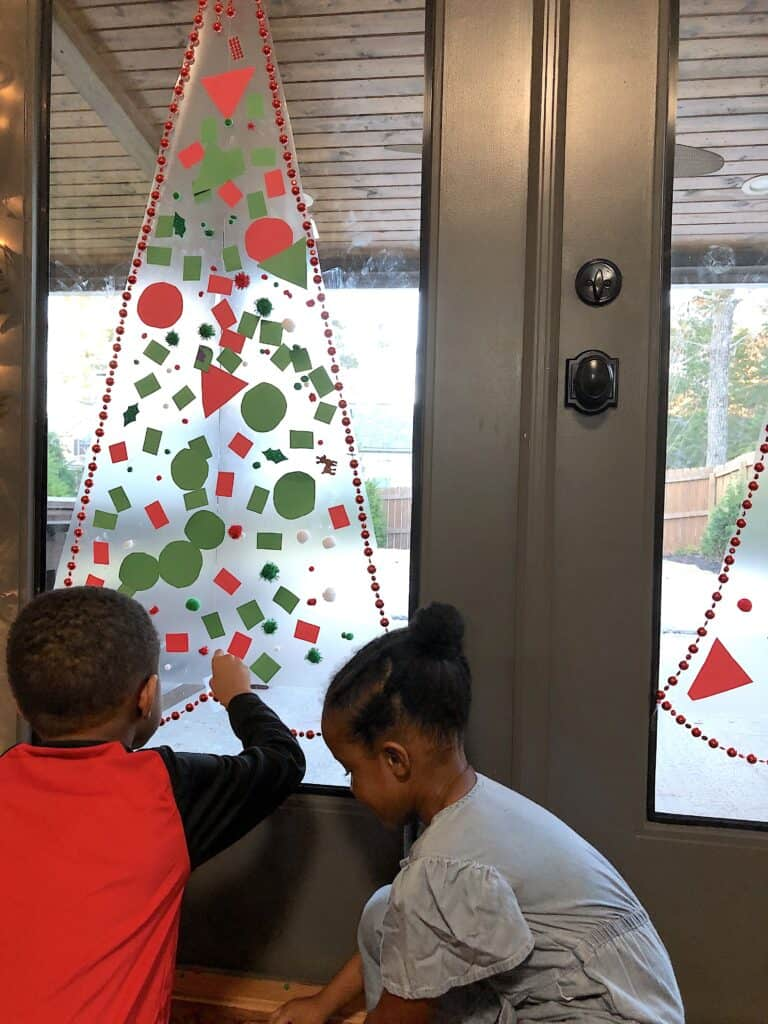 This Christmas Tree Craft For Kids Will Be A Hit For The Holidays! This Activity Uses Contact Paper To Create A Fun And Unique Christmas Craft Experience. #christmascrafts #christmascraftsforkids